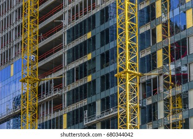 Building under construction stories with yellow crane mast attached on the side