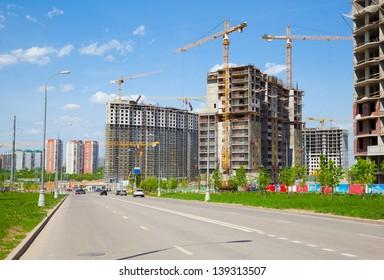 Building under construction, yellow construction crane, street.