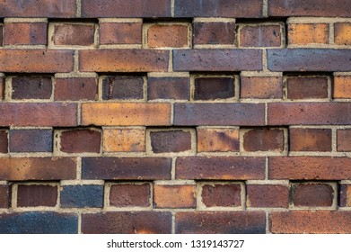 Building wall made of dark, yellow to brownish clinker bricks with various alternating patterns. The stones are offset in rows, turned, indented or omitted.