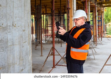 Building works. Inspection at a construction site.Acceptance of construction work.A man with a tablet at a construction site.Bureau of Architecture.Checking the building company.Checking the developer