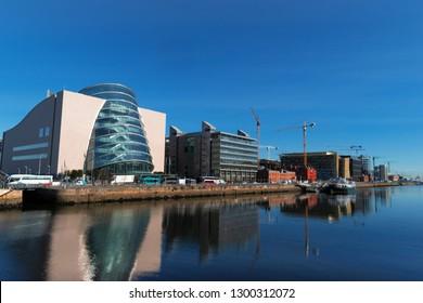 Buildings along the quay of the port. Crane, boats, traffic, blue sky. Dublin, Ireland, Europe.
