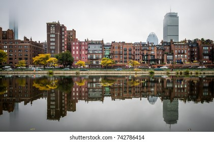 Buildings along river with glasslike reflection and trees turning leaves fall season.