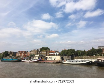 Buildings and boats on the river Thames a cloudy summer's day