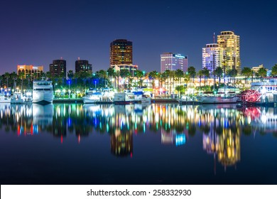 Buildings and boats reflecting in the harbor at night, seen from Shoreline Aquatic Park in Long Beach, California.