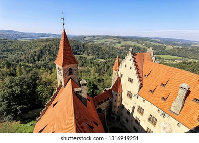 Buildings of Bouzov castle from above with woods and villages in background