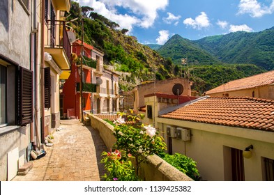 Buildings with colorful walls and orange tiled roofs in seaside small town Scilla on shore of Tyrrhenian sea with view of green hills Aspromonte National Park and blue sky, Calabria, Southern Italy