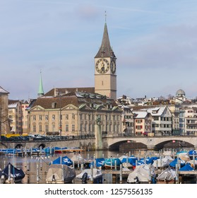 Buildings of the historic part of the city of Zurich along the Limmat river in winter, tower of the St. Peter Church above them, the Munsterbrucke bridge.