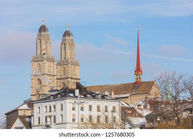 Buildings of the historic part of the Swiss city of Zurich along the Limmat river in winter, towers of the famous Grossmunster cathedral above them.