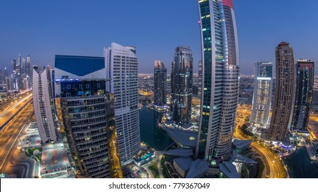 Buildings of Jumeirah Lakes Towers after sunset with traffic on the road day to night transition timelapse. The JLT is a large development which consists of 79 towers being constructed along the edges