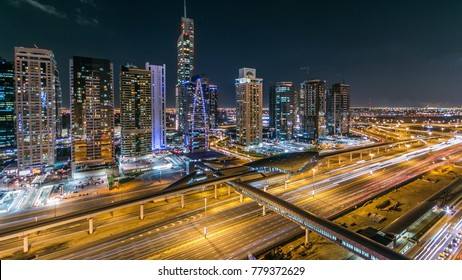 Buildings of Jumeirah Lakes Towers with traffic on the road night timelapse. The JLT is a large development which consists of 79 towers being constructed along the edges of 3 artificial lakes and park