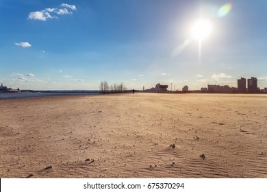 Buildings and a lake in background of the desert. Neighborhood of city and desert concept. Wide embankment full of sand. Abandoned deserted district of town. Mystic lonely black figure in the distance