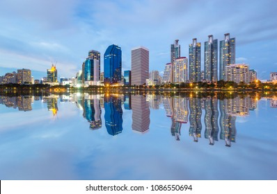 Buildings and lights in the city after sunset have reflect in the lake foreground.