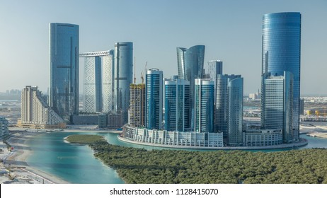 Buildings on Al Reem island in Abu Dhabi timelapse from above. Aerial citiscape of Al Reem Island at morning, showing the reflection on skyscrapers.