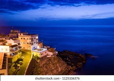 Buildings on the rocks and Atlantic ocean night scene. Puerto de Santiago. Tenerife islans, Canarias, Spain