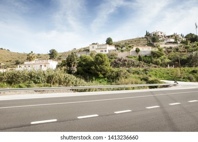 buildings on side of hill in almunecar spain with a main road in front
