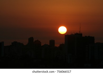 the buildings with the orange sun behind, backlight