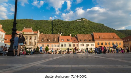 Buildings and people in the main square and mountain with sign of Brasov, Romania 20.08.2017