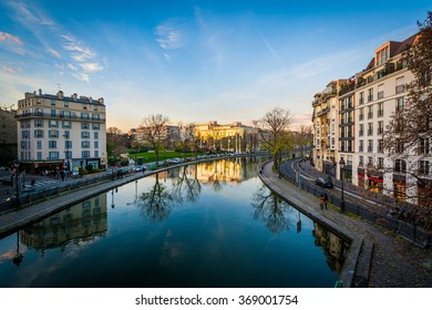 Buildings reflecting in Canal Saint-Martin at sunset, in Paris, France.