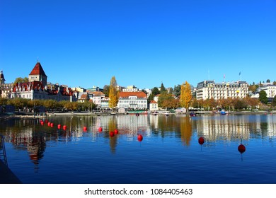 Buildings reflection in the lake. Sunny day with blue sky of Geneva lake or Lac Leman in late summer and beginning of autumn. Lausanne, Switzerland