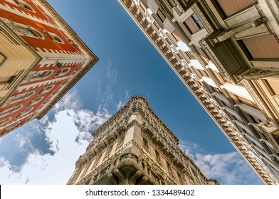 Buildings in Trieste, Italy, from below, during the daylight. Frog perspective gives view on architecture of three surrounding objects creating golden section and rule of thirds composition scene.