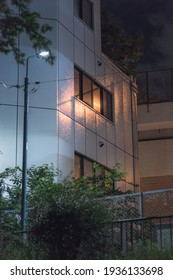 A building's wall is reflecting luminous ray of light from the street lamp in the streets of Tokyo by night during summer.