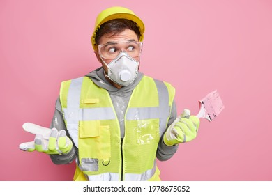 Buillding improvement and redecoration concept. Puzzled hesitant handyman in working clothes holds paint brush has clueless surprised expression poses against pink background. Shocked repairman