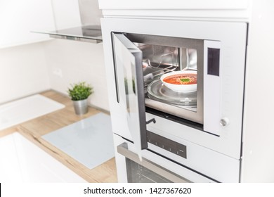Built-in microwave oven  in the kitchen with tomato soup in white plate.
