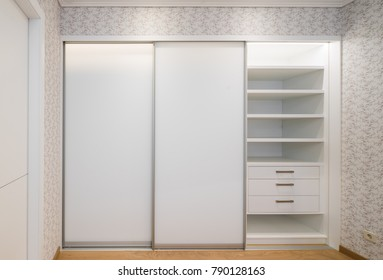Built-in sliding wardrobe, white color.