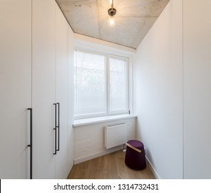 Built-in wooden wardrobe white color in the hallway.