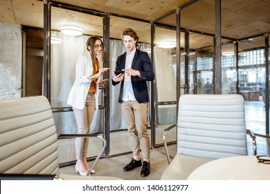 Buiness man and woman having a business convesation standing in the meeting room of the modern office
