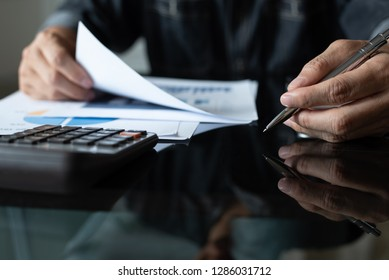 Buisness analysis. Businessman working in modern office reviewing business marketing report on glass desk with reflection and copy space, close up. drak tone