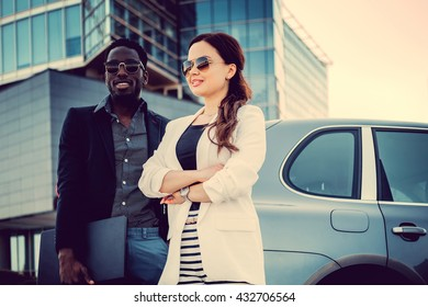 Buisness couple near car in downtown.