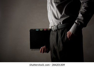 A buisness man holding a spiral diary in a hand and the other in his pocket over dark gray background