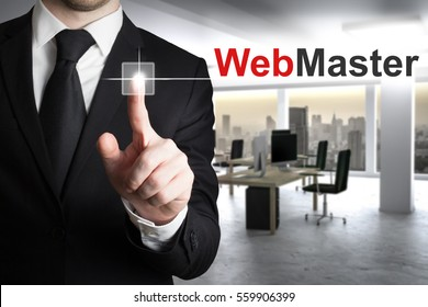 buisnessman in large modern it office pushing button webmaster skyline