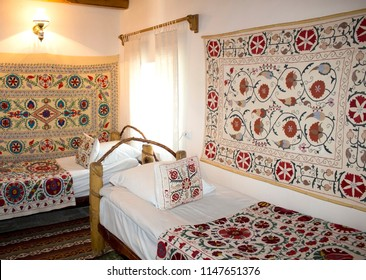 "Bukhara, Uzbekistan - 14 June, 2018: The room of the guest house ""Amulet"". Traditional Uzbek furniture wooden beds, embroidered suzani. Countryside vintage style."