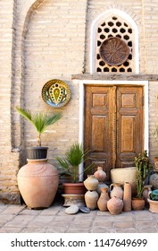 "Bukhara, Uzbekistan - 16 June, 2018: The decor of the patio of the guest house ""Amulet"". Clay pots, palm trees. Mediterranean style. Arabic influence on the traditional Uzbek culture."