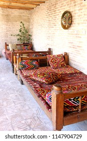 "Bukhara, Uzbekistan - 16 June, 2018: The patio of the guest house ""Amulet"". Traditional Uzbek furniture wooden beds called tapchans covered kurpacha. Countryside vintage style."