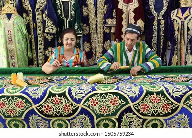 Bukhara, Uzbekistan. 24.03.2018 year.A man and a woman in traditional clothes embroider a gold-embroidered carpet in their workshop in Bukhara, Uzbekistan