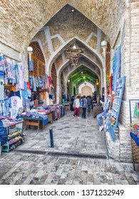 BUKHARA, UZBEKISTAN - APRIL 07, 2019: The narrow pass at trading dome market with the numerous tourist stalls in Bukhara, Uzbekistan