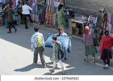Bukhara, Uzbekistan - April, 2019: Uzbek she-toreador. Street souvenir sellers and tourists.