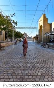 Bukhara, Uzbekistan - July 12, 2019: Woman walking along the streets of old Bukhara, Uzbekistan.