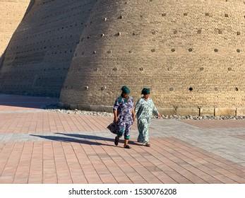 Bukhara, Uzbekistan - July 12, 2019: Local women walking along the wall of the Bukhara Fortress (Ark), Uzbekistan. The Ark of Bukhara is a massive fortress located in the city of Bukhara, Uzbekistan.