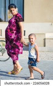 BUKHARA, UZBEKISTAN - JUNE 6, 2011: Unidentified Uzbek woman and her son walk in the street in Uzbekistan, Jun 6, 2011.  81% of people in Uzbekistan belong to Uzbek ethnic group