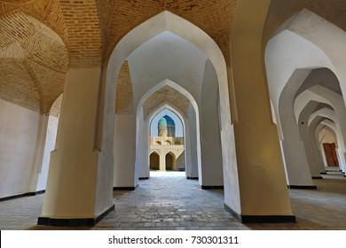 BUKHARA, UZBEKISTAN - OCTOBER 7, 2017: Arches of Poi Kalon mosque and its blue dome through archways, in Bukhara, Uzbekistan.