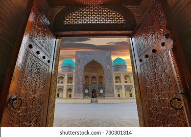 BUKHARA, UZBEKISTAN - OCTOBER 8, 2017: View over Poi Kalon theological school at the sunrise, through wooden doors of the mosque in Bukhara, Uzbekistan.