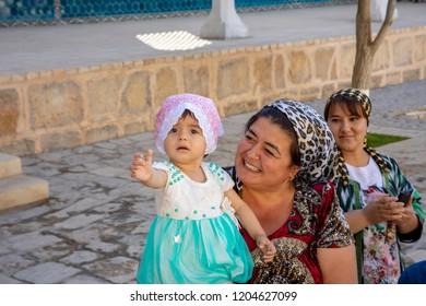 Bukhara, Uzbekistan - September 23, 2018 :  Young child wiht women at the Mausoleum of Bahouddin Nakshband, or Bakhuddin Nakshbandi, founder of Sufism in Bukhara, Uzbekistan.