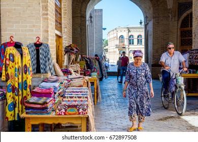 BUKHARA, UZBEKISTAN - SEPTEMBER 4: Street bazaar with souvenirs and traditional uzbek clothes in Bukhara downtown. September 2016