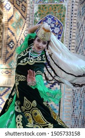 Bukhara, Uzbekistan.14.10. 2018. A woman in Bukhara national costume shows a dance on the background of ancient architecture .Folklore festival in Bukhara, Uzbekistan