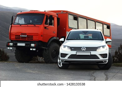 Bukhara/Uzbekistan-10.01.2017: white SUV volkswagen touareg stands at the exit of the mountain road next to a large shift truck KAMAZ