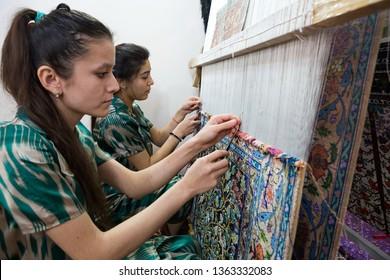 Bukhara.Uzbekistan.26.03.2018.Uzbek women weaving silk carpets in a workshop in Bukhara.